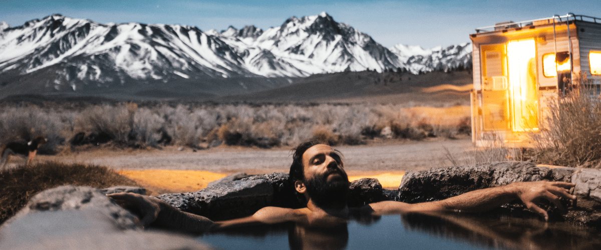 Man relaxing in water near mountains